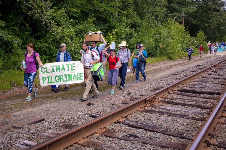 "Protesters march during a ""climate pilgrimage"" along railroad tracks that lead to the Merrimack Station, a coal-fired power plant, in Bow on Saturday, July 15, 2017. (ELIZABETH FRANTZ / Monitor staff)"